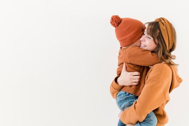 Zijaanzicht moeder met zoon in haar armen