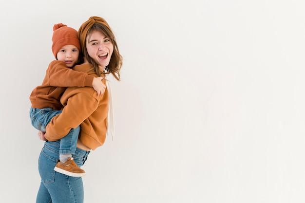 Zijaanzicht moeder met zoon op de rug rit