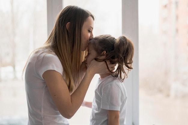 Zijaanzicht moeder zoenen meisje
