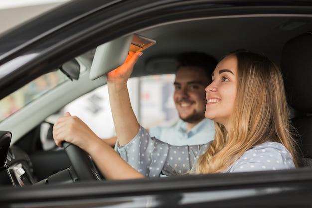 Zijaanzicht mooie blonde vrouw in auto