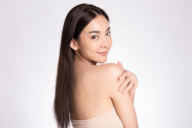 Zijaanzicht mooie jonge aziatische vrouw aan te raken haar lichaam met verse gezonde huid, geïsoleerd op een witte muur, schoonheid cosmetica en gezichtsbehandeling concept