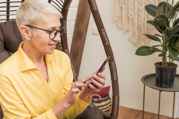 Zijaanzicht mooie senior vrouw met behulp van haar telefoon