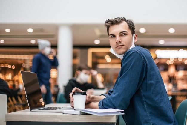 Zijaanzicht. nadenkende jonge man zit aan een tafel in een café