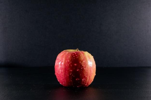 Zijaanzicht natte rode appel op zwart
