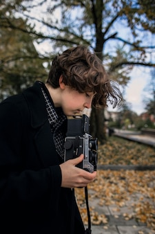 Zijaanzicht niet binaire persoon die een retro camera aanpast