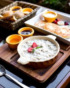 Zijaanzicht ontbijt ingesteld havermout met aardbeien honing jam kaas pannenkoeken bessen en banaan op een dienblad