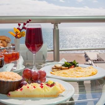 Zijaanzicht ontbijt met gebakken en druiven en omelet in witte plaat op de baly on the sea