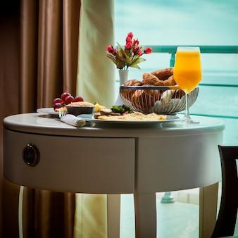 Zijaanzicht ontbijtomelet met champignons, sap, croissants in roomservice in hotel met prachtig uitzicht op zee
