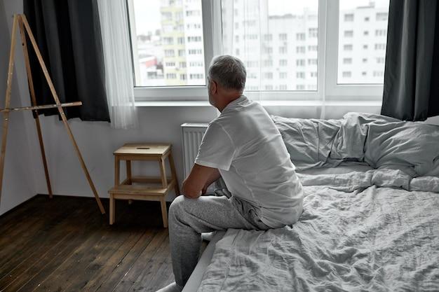 Zijaanzicht op boos man zit alleen op bed thuis in de donkere kamer, 's ochtends alleen.