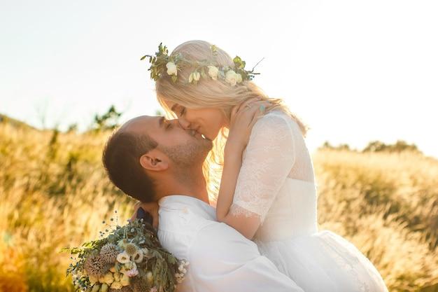 Zijaanzicht op bruid en bruidegom hand in hand in zonnige zomerdag outdoor bruiloft en relatie