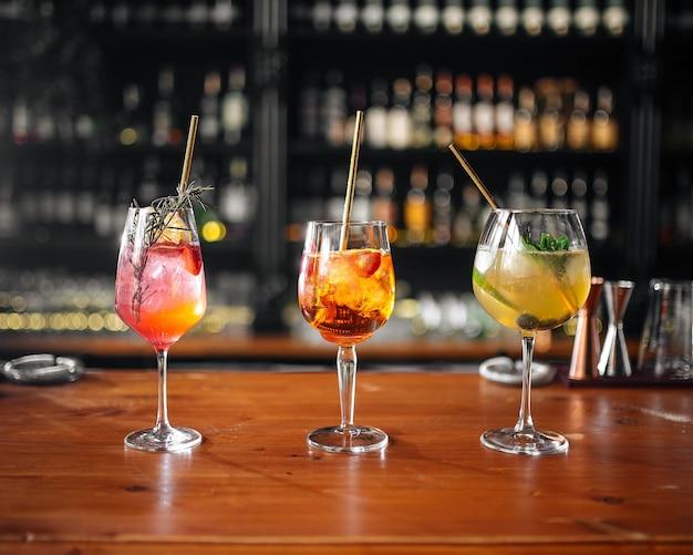 Zijaanzicht op drie glazen verschillende fruitcocktails op de bar