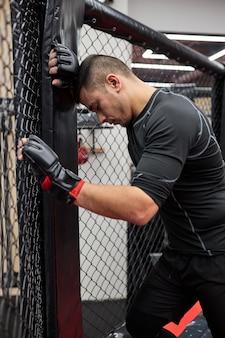 Zijaanzicht op fitness sportieve vermoeide man tijd doorbrengen in de sportschool boksen beoefenen, rusten, een pauze nemen. training sport motivatie concept