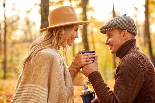Zijaanzicht op gelukkige paar hete thee drinken in de herfst bos