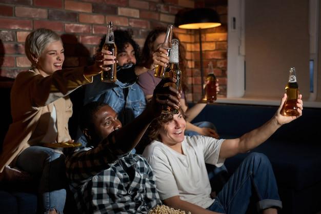 Zijaanzicht op gelukkige studentenmannen en -vrouwen die hun favoriete sportteam ondersteunen, bier drinken, samen emotioneel juichen, thuis op de bank zitten in vrijetijdskleding