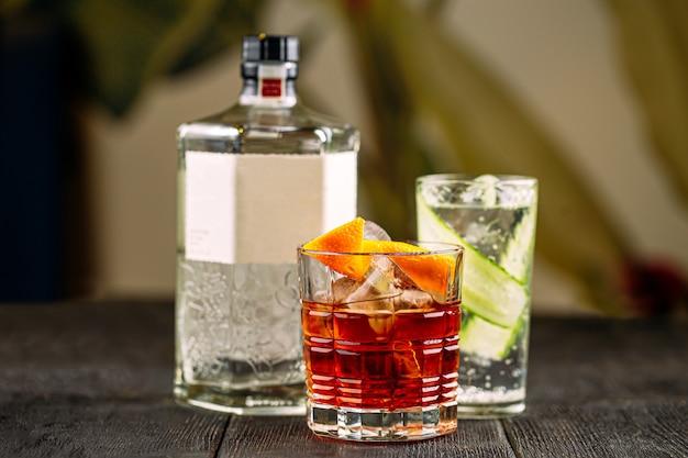 Zijaanzicht op gin-cocktails in glazen met fles op de houten tafel