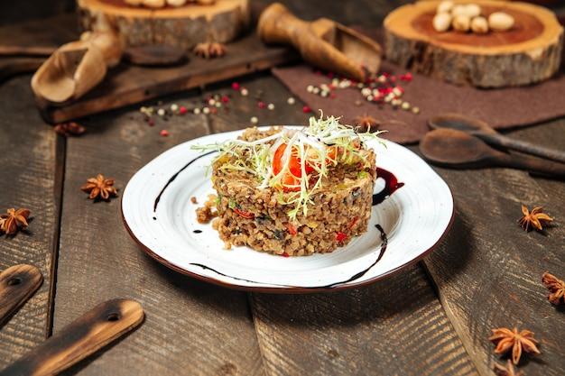 Zijaanzicht op gourmet boekweit garnituur met groenten en champignons