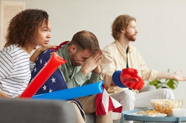 Zijaanzicht op groep teleurgestelde mensen die thuis naar sportwedstrijden op tv kijken en het verliezen van beweging bespreken terwijl ze fanartikelen dragen