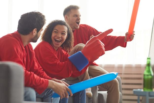 Zijaanzicht op groep vrienden kijken naar sportwedstrijd op tv thuis en emotioneel juichen terwijl ze rode teamuniformen dragen