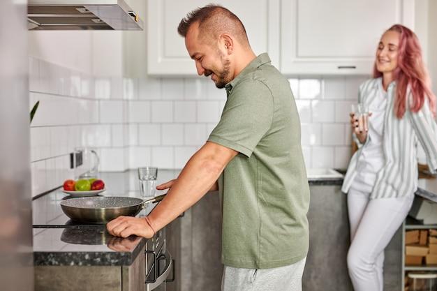Zijaanzicht op het mannelijke koken in de keuken terwijl zijn vrouw op het achtergrond drinkwater staat