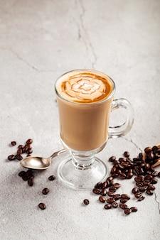 Zijaanzicht op ingerichte koffie latte in een glazen mok op het betonnen oppervlak