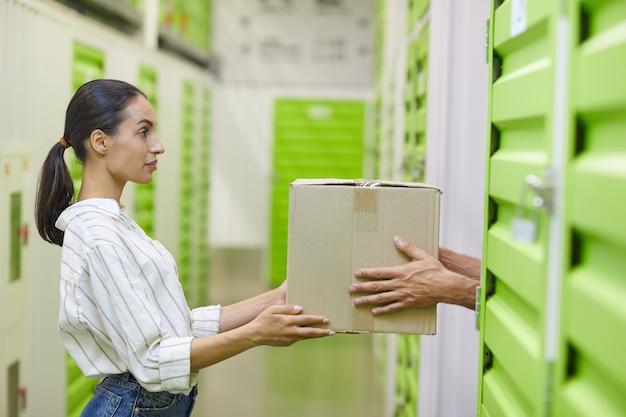 Zijaanzicht op jonge vrouw met kartonnen doos en inleveren aan de mens tijdens het inpakken van zelfopslageenheid, kopie ruimte