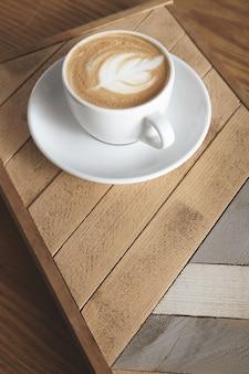 Zijaanzicht op kop met romige cappuccino latte met melkachtig schuim bovenop in bladvorm geïsoleerd op houten plaat met patroon. op tafel in café winkel presentatie.
