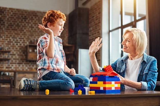 Zijaanzicht op lachende grootmoeder en een roodharige kleine jongen die elkaar aankijken en een high fie geven terwijl ze hun succes vieren bij het bouwen van een droomhuis