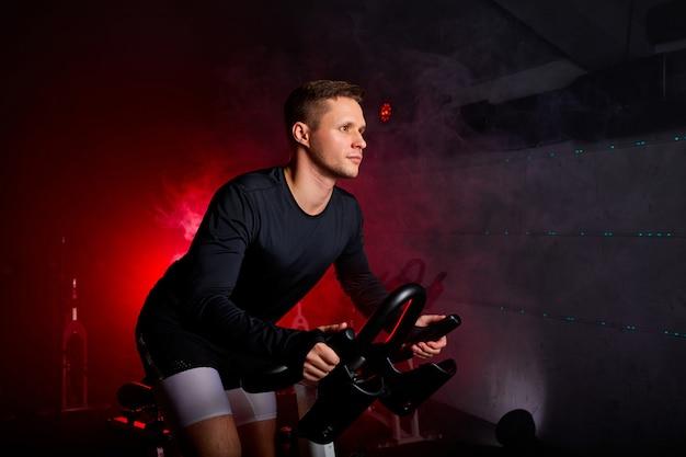 Zijaanzicht op man stationaire fiets rijden in health club, vooruit kijkend, in trainingspak