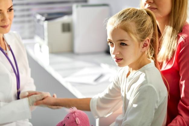 Zijaanzicht op meisjespatiënt bij gebruikelijke medische inspectiecontrole, vriendelijke minzame arts en patiënt in kliniek, vrouwelijke kinderarts die hand van meisje, glimlach houdt. geneeskunde, gezondheidszorgconcepten