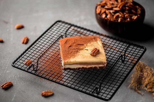 Zijaanzicht op niet-gebakken milieuvriendelijke pecannootcake op metalen gaasblad