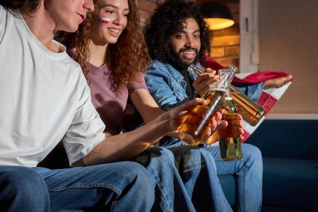 Zijaanzicht op opgewonden vrienden die flessen bier rammelen tijdens sportwedstrijd op tv, juichen voor het beste amerikaanse team, anticiperend op het doel. focus op flessen