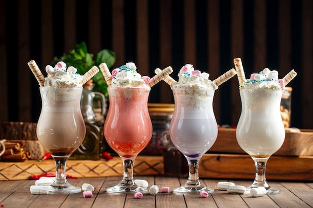 Zijaanzicht op verschillende zoete milkshakes op de houten achtergrond
