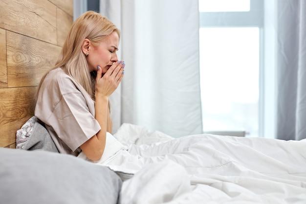 Zijaanzicht op vrouw ziek met griep thuis zittend op bed alleen, met pijn in de keel. zieke blanke vrouw met seizoensgebonden infecties, griepallergie en loopneus. coronavirus (covid-19