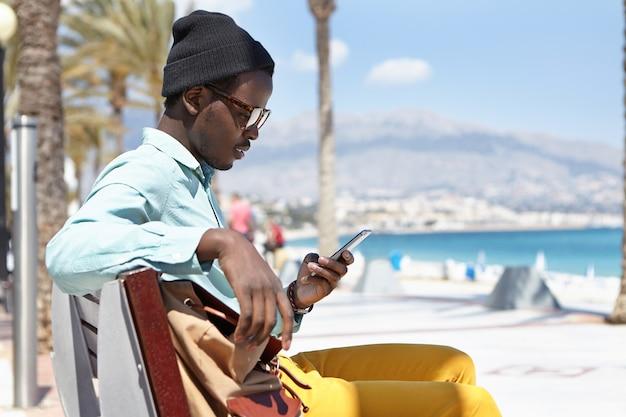 Zijaanzicht openluchtportret van vrolijke stijlvolle jonge afro-amerikaanse man zittend op bankje langs promenade aan zee, met gratis wifi in de stad terwijl hij met vrienden chat via sociale netwerken op mobiele telefoon