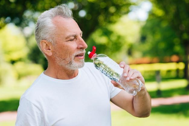 Zijaanzicht oude man drinkwater