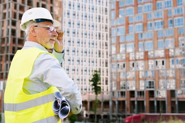 Zijaanzicht oude man met bril en helm