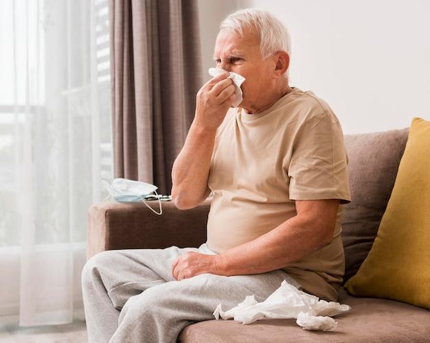 Zijaanzicht oude man zijn neus snuiten
