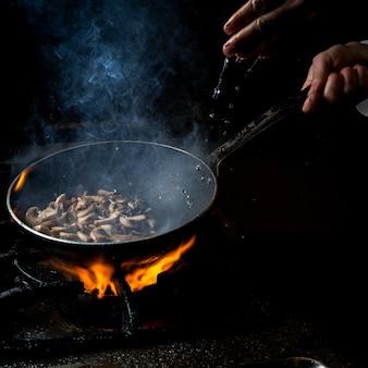 Zijaanzicht paddenstoel bakken met waterdruppel en vuur en mens hand in pan