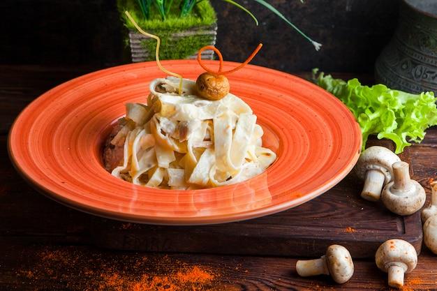 Zijaanzicht pasta met saus, parmezaan, champignons, sla