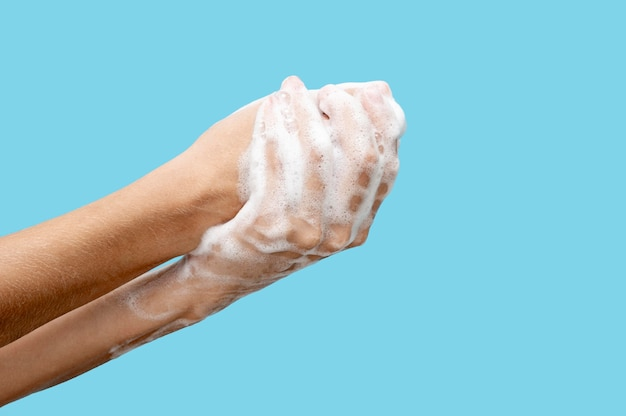 Zijaanzicht persoon die zeep gebruikt om zijn handen te wassen