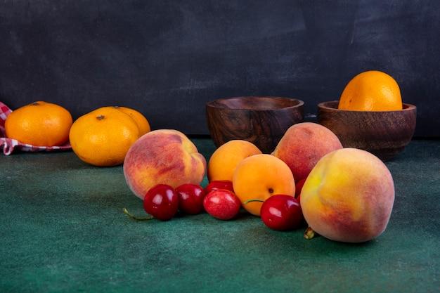 Zijaanzicht perziken met abrikozen en kersen en mandarijnen in een kom