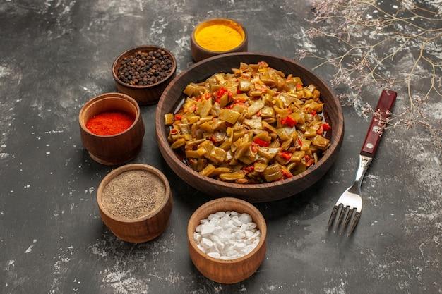 Zijaanzicht plaat van bonen plaat van sperziebonen en tomaten naast de kommen met kruidentakken en vork op de donkere tafel