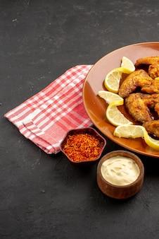 Zijaanzicht plaat van fastfood kippenvleugels frietjes met citroen en kommen met sauzen en kruiden op roze-wit geruit tafelkleed aan de rechterkant van zwarte tafel
