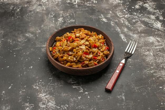 Zijaanzicht plaat van sperziebonen houten plaat van sperziebonen en tomaten naast de vork op de donkere tafel