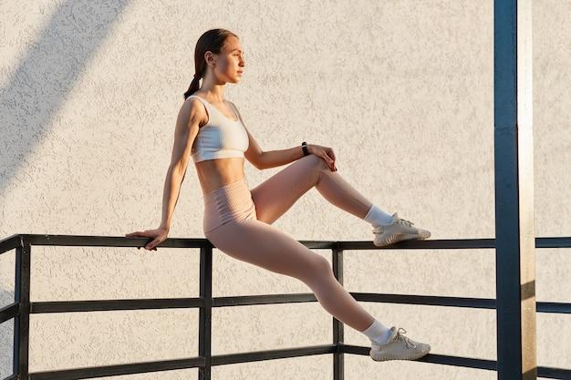 Zijaanzicht portret van aantrekkelijke mooie vrouw zittend op de reling en wegkijken, stijlvolle sportieve kleding dragen, ontspannen na het sporten buiten.