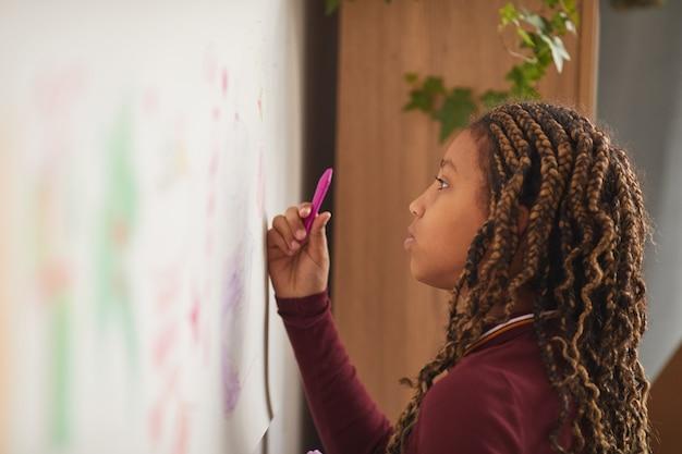 Zijaanzicht portret van afrikaans-amerikaans meisje puttend uit muur thuis of in de kunstklasse, kopie ruimte