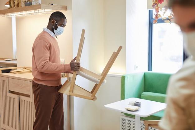 Zijaanzicht portret van afro-amerikaanse man met masker in café en het schikken van meubels terwijl hij zich voorbereidt op opening in de ochtend, kopieer ruimte