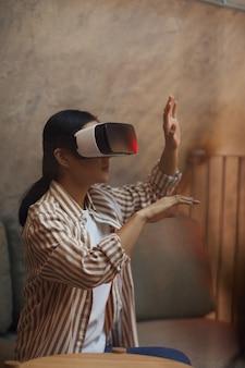 Zijaanzicht portret van aziatische vrouw vr-uitrusting dragen en gebaren terwijl u geniet van meeslepende ervaring in futuristisch interieur