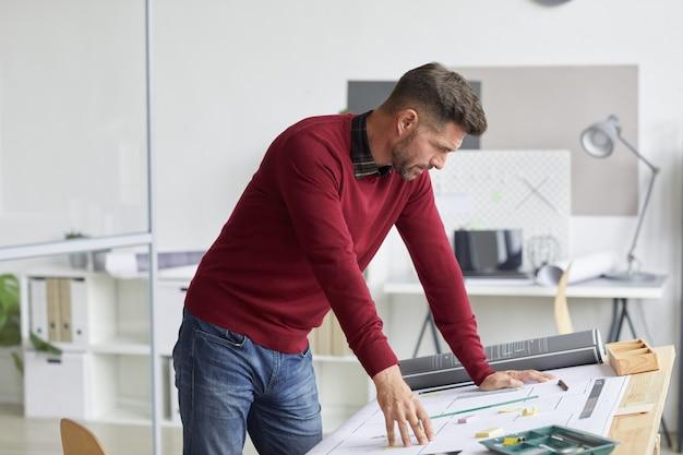 Zijaanzicht portret van bebaarde architect blauwdrukken kijken terwijl leunend op de tekentafel op de werkplek,