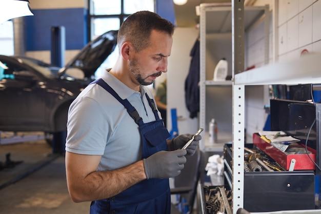 Zijaanzicht portret van bebaarde automonteur tools kiezen tijdens het repareren van voertuig in garage winkel, kopie ruimte
